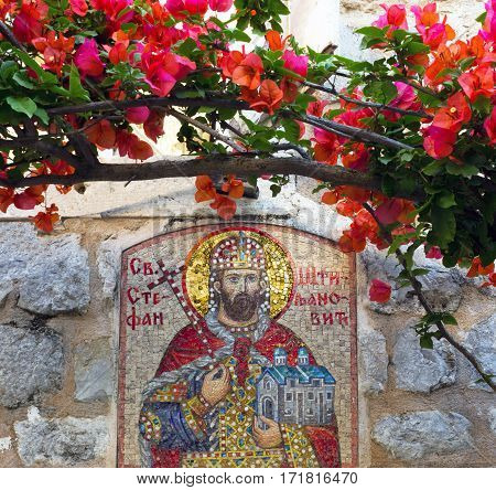 Budva, Montenegro - July 3, 2016: Orthodox icon of Saint Stephen and bougainvillea old town of Budva