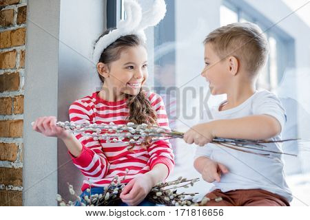 Cute smiling boy and girl holding catkins and looking at each other