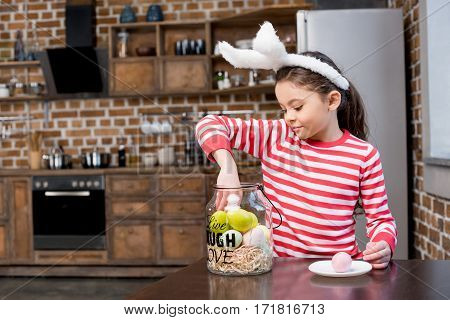 Beautiful little girl in bunny ears with glass jar full of painted easter eggs