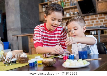 Cute little kids painting easter eggs with paint brushes