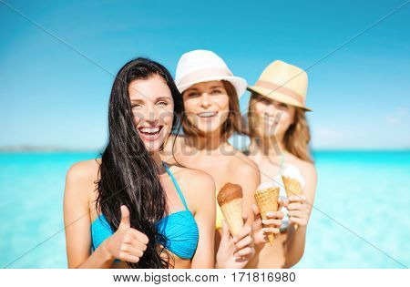 summer holidays, vacation, travel and people concept - group of smiling young women with ice cream showing thumbs up on beach over sea and blue sky background