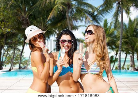 summer holidays, vacation, food, travel and people concept - group of smiling young women eating ice cream over exotic tropical beach with palm trees and pool background