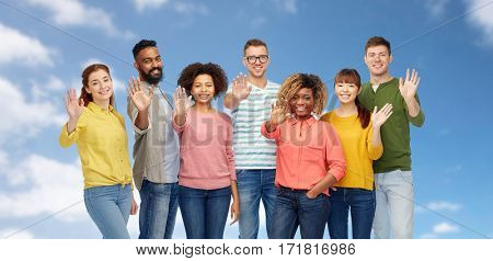 diversity, race, ethnicity and people concept - international group of happy smiling men and women waving hand over blue sky and clouds background