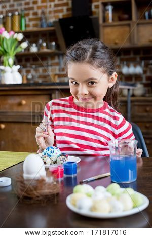 Adorable little girl painting easter eggs and smiling at camera