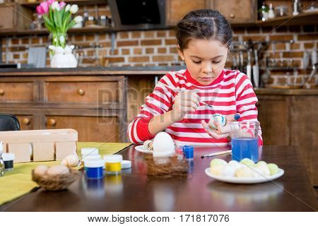 Adorable little girl painting easter egg in kitchen