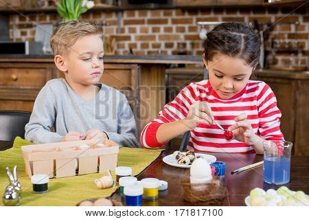 Little boy looking at cute smiling girl painting easter egg