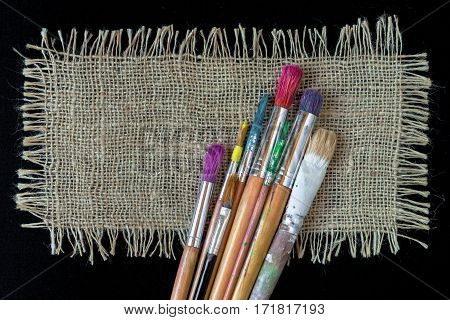 Brushes for painting artist and a piece of linen cloth lying on a black background