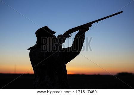 Hunter's silhouette at sunset shooting a gun