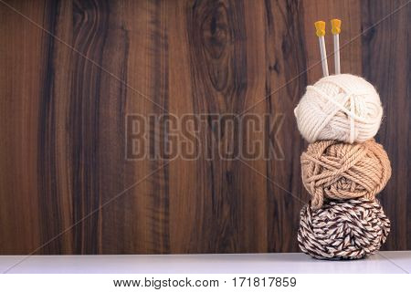 Three Threads For Knitting White And Brown Colors And Spokes On Wooden Brown Background With Pattern.