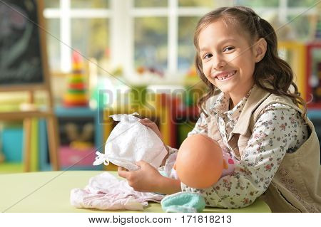 Portrait of a cute little girl playing with doll