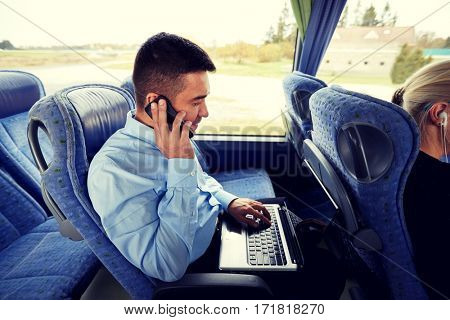 transport, tourism, business trip and people concept - man with smartphone and laptop calling in travel bus