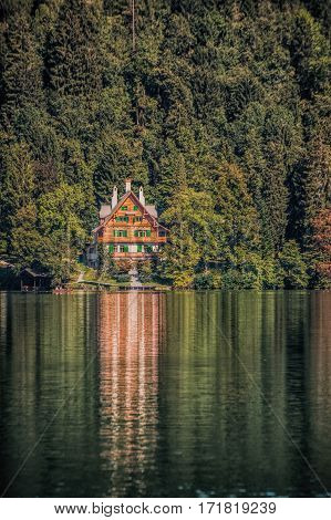 House at the shore of Bled lake with reflection.