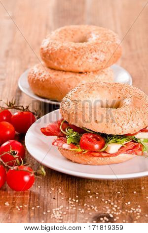 Sesame bagels with pepperoni and cherry tomatoes.