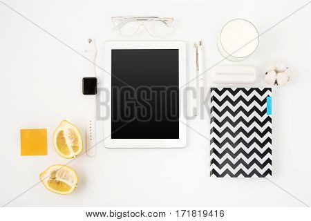 Top view of white female office table with laptop, notebook, wrist watch, pen, pencil, glasses, milk, fruits