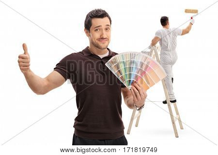 Man holding a color swatch and giving a thumb up with a painter painting climbed up a ladder isolated on white background