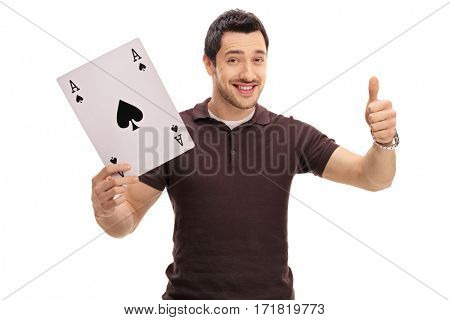 Joyful guy holding a big ace of spades card and giving a thumb up isolated on white background