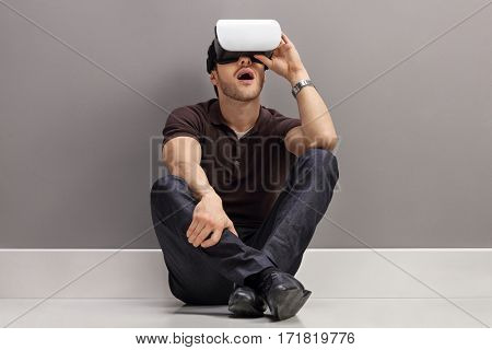 Amazed guy seated on the floor using a VR headset and leaning against a gray wall