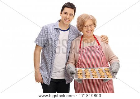 Young man and an old lady with a tray of freshly baked cookies isolated on white background