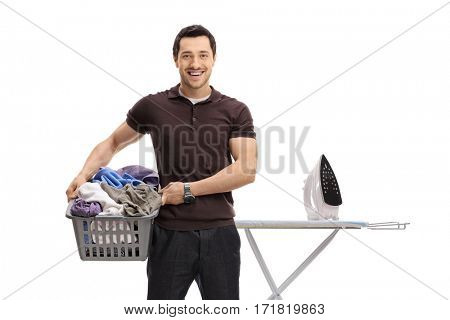 Guy holding a laundry basket full of clothes in front of an ironing board isolated on white background