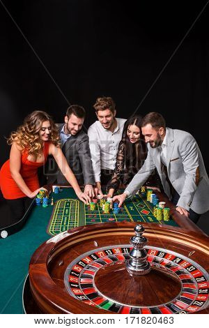 Group of young people behind roulette table on black background. young people are betting in the game