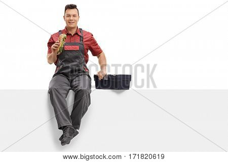 Young worker holding a sandwich and sitting on a panel next to a toolbox isolated on white background