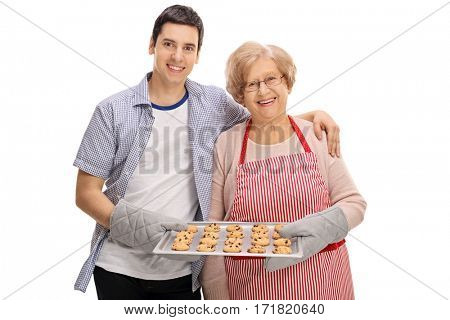 Cheerful young man and an elderly lady holding a tray of freshly baked cookies isolated on white background