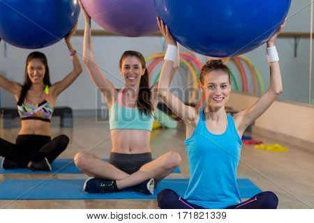 Group of women exercising with exercise ball in gym