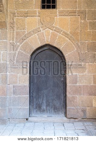 Wooden aged vaulted ornate door and stone wall Medieval Cairo Egypt