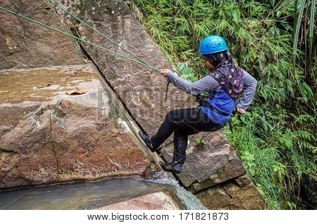 Beaufort,Sabah,Malaysia-Jan 28,2017:A muslim teenager girl enjoying to abseil down a waterfall in Beaufort,Sabah,Borneo.Waterfall Abseiling activity adventure getting famous in Sabah,Malaysia.