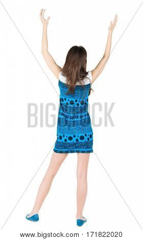 back view of surprised brunette woman with hands up. Girl in blue dress. Rear view. Isolated over white background.