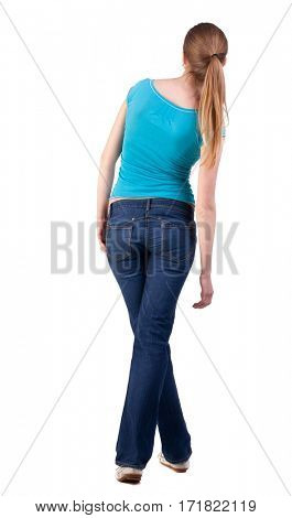 back view of standing young beautiful  blonde woman in blue t-shirt and jeans. girl  watching. Rear view people collection.  backside view of person.