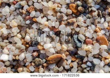 Naturally rounded gravel at sea shore, nature beach background texture