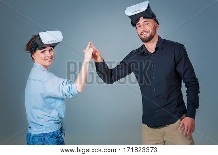 Excited young man and woman having fun with a VR glasses. Emotions couples. Gray background