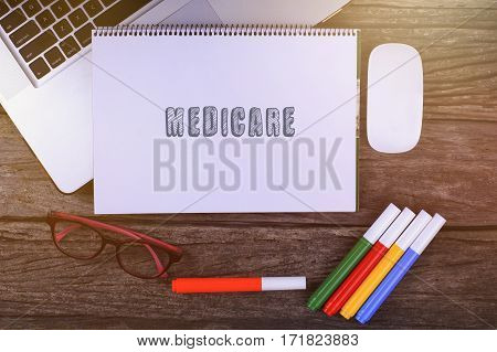Medicare Text On Wooden Desk With Tablet Pc And Keyboard.
