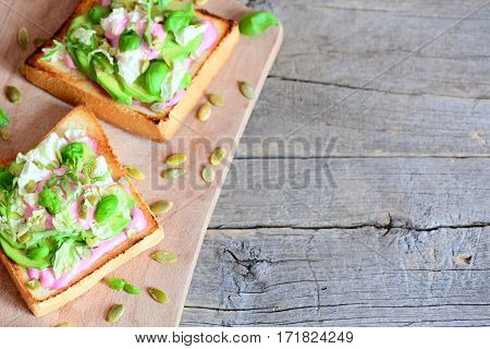Avocado sandwiches on a wooden board and on a vintage background with copy space for text. Homemade open sandwiches with avocado, pumpkin seeds, lettuce, basil and cream. Healthy food