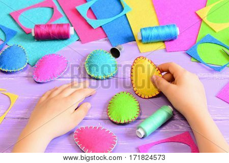 Child hold a felt Easter egg in his hand. Small child made Easter crafts of felt. Tools and materials for handicraft on wooden table. Easy fun kids crafts concept