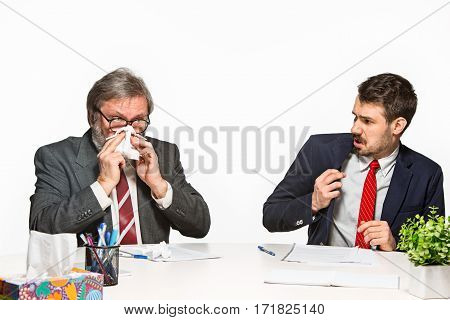 The two colleagues working together at office on white studio background. The one sneezing sick man - the other is afraid to be ill