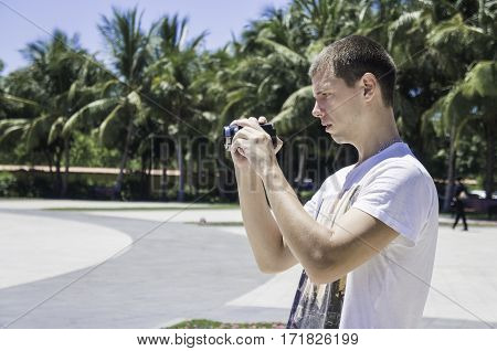 male photographer side view of a man holding a camera in his hands.