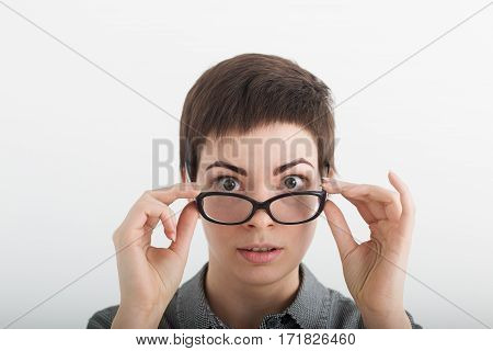 Close up of strict surprised young funny female teacher or student in glasses isolated on white background, looking over her glasses.
