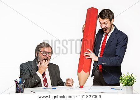 The two colleagues working together at office on white studio background. They signing a document with large toy pencil
