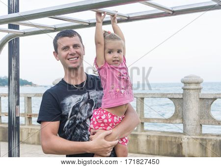 Dad And Daughter Playing Promenade By The Sea. Young Man, Little Girl Hanging On The Bar.