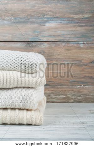Knitted wool sweaters. Pile of knitted winter clothes on wooden background sweaters knitwear space for text