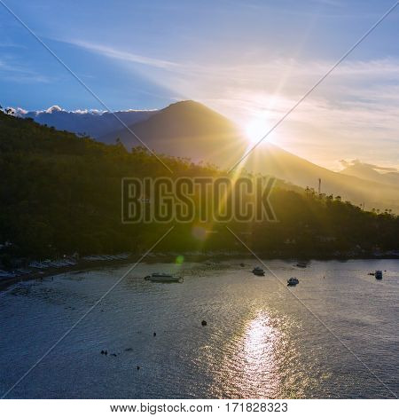 Sunrise over Gunung Agung volcano and Jemeluk Beach near Amed village, East of Bali, Indonesia.