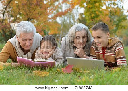 grand parents spending time with grandchildren outdoors in autumn