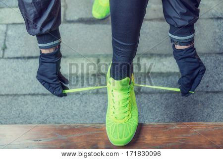Urban jogger tying running shoes on a bench.