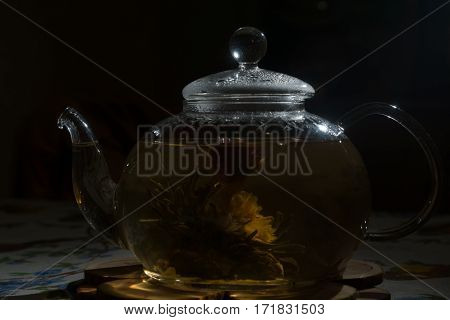 The glass teapot is on the table