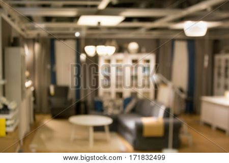 Abstract blurred background of modern living room with chairs sofa torchere from furniture showroom.