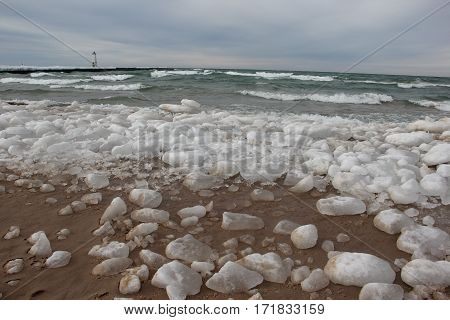 A winter beach with ice and snow with the Frankfort, MI lighthouse in the background.