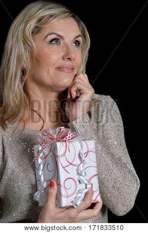 Portrait of a senior woman with present against black