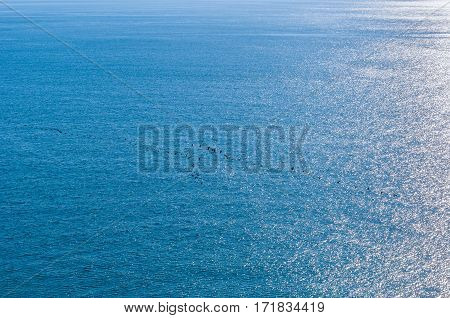 A beam of sunlight reflecting over rippled blue water